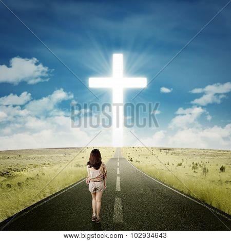 Casual Girl Walking Toward A Cross