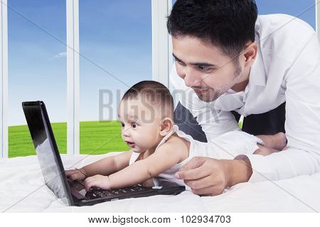 Cheerful Baby Typing On Laptop With Dad