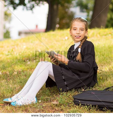 Small Student Girl Sitting On Grass And Using Tablet Pc