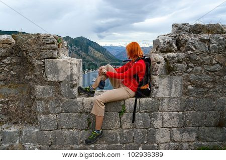 Girl Tourist Looks At Bay Of Kotor From Wall Of Ancient Fortress