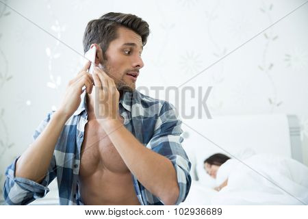 Portrait of a handsome man talking on the phone while his wife sleeping in the bed at home