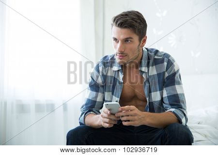 Portrait of a thoughtful man sitting on the bed with smartphone and looking away at home