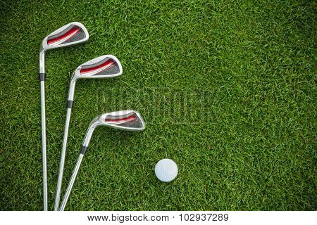 Golf clubs and ball in grass, shot from aerial view