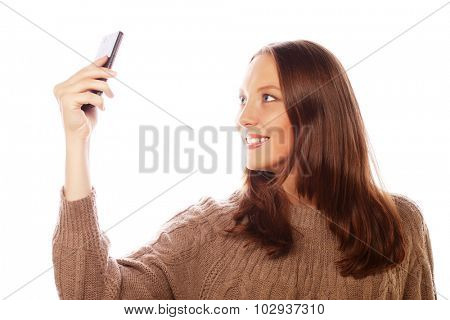People, lifestyle and tehnology concept: pretty woman taking selfies with her smart phone - isolated on white