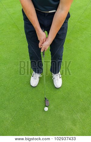 Golf player holding club, ready to hit ball