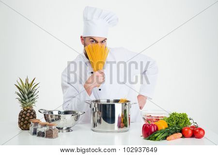 Portrait of a male chef cook covering face with pasta isolated on a whtie background