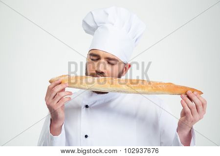 Portrait of a male chef cook smelling fresh bread against white background