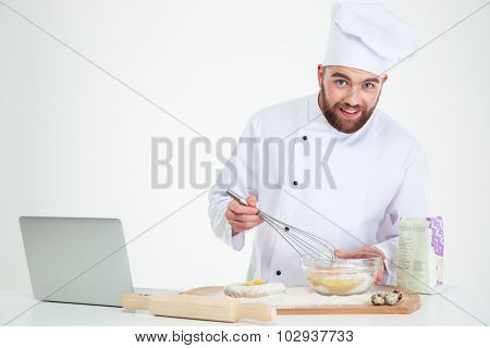 Portrait of a smiling male chef cook baking with laptop isolated on a white background