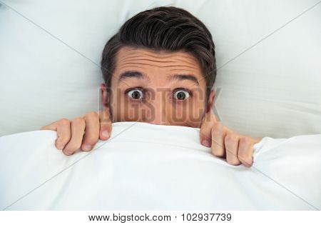 Man hiding in bed under the blanket at home
