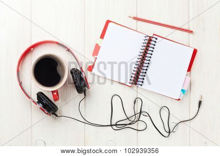 Headphones, coffee cup and notepad on wooden table. Top view with copy space