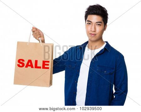 Man hold with shopping bag and showing a word sale