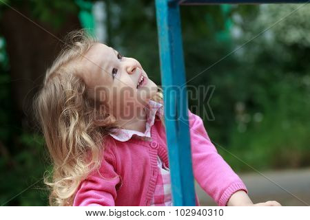 Head and shoulders portrait of looking up little blonde girl on playground