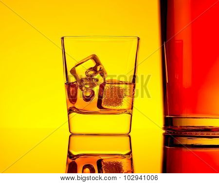 One Glass Of Whiskey With Ice Cubes Near Bottle On Table With Reflection, Warm Yellow Tint Atmospher