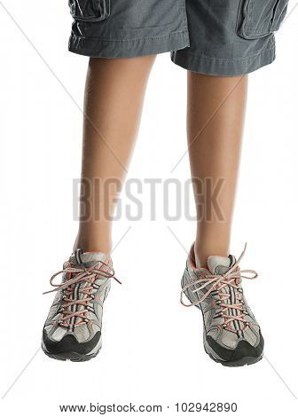 Child wearing hiking shoes jumps isolated on white background.