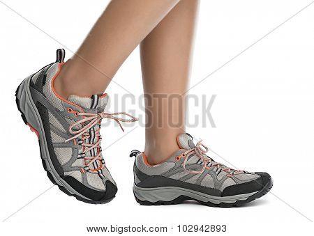 Child wearing sports shoes walking on white background