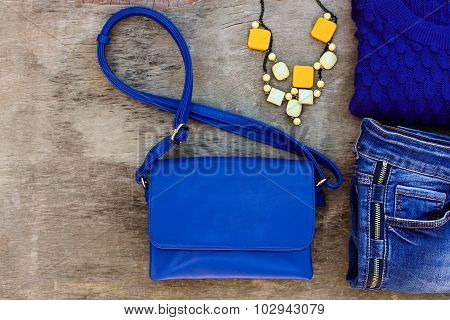 Women's autumn clothing and accessories: blue sweater, jeans, handbag, beads on wooden background.