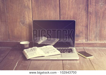 Laptop, Book And Cell Phone On A Wooden Floor