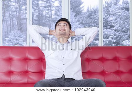 Man Sitting On Sofa And Daydreaming