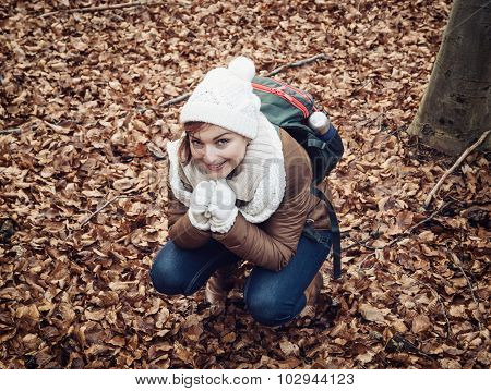 Young Woman In White Cap Squats In The Brown Leaves At The Forest