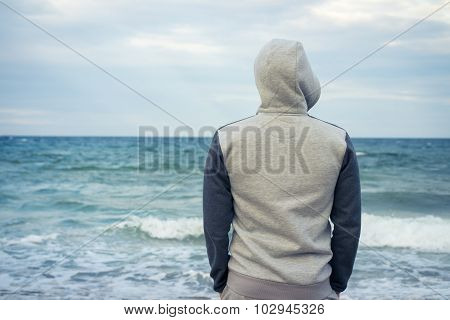 Man Stands On The Beach In A Tracksuit With A Hood And Looking At The Sea