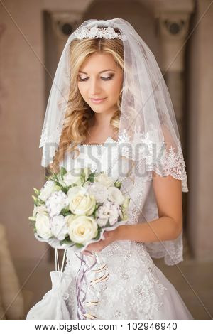 Beautiful Bride Woman With Bouquet Of Flowers, Wedding Makeup And Hairstyle, Bridal Veil. Girl Weari