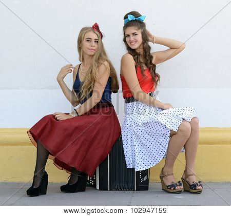 two girls sitting on old accordion