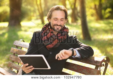 Middle-aged man resting on the bench outdoors