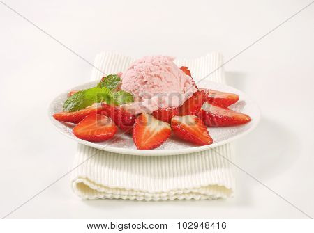 plate of halved strawberries with a scoop of pink ice cream on white place mat
