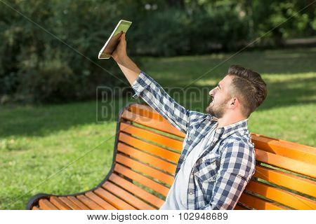 Young man making selfies on the bench outdoors