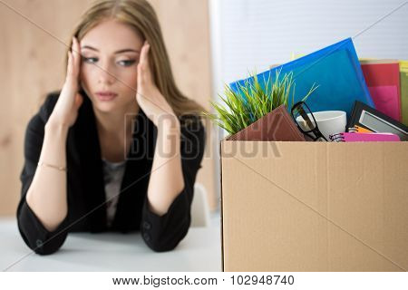 Young Dismissed Female Worker Sitting Near The Carton Box With Her Belongings