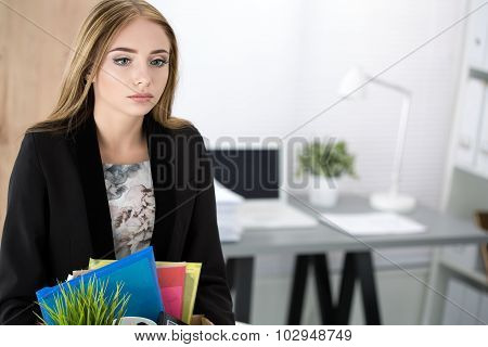 Young Dismissed Female Worker In Office Holding Carton Box With Her Belongings