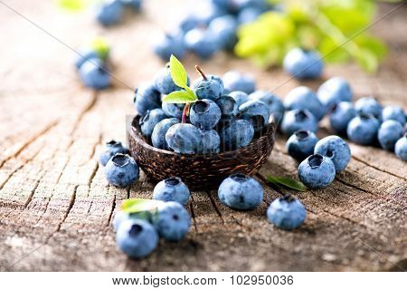 Blueberry. Freshly picked blueberries over wooden table. Juicy and fresh blueberries with green leaves in wooden bowl. Rustic Background. Concept for healthy eating and nutrition
