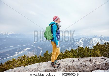 Side view of young woman wearing pink hat, blue jacket, green backpack, yellow pants and hiking boots standing against winter mountain valley - adventure concept