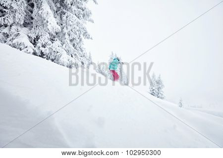 Back view of female snowboarder having fun in deep backcountry powder snow during winter blizzard in Alps - extreme sports concept