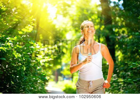 Beauty young smiling woman running outdoor over sunrise. Brunette model girl jogging in the park and enjoying nature. Female training and listening to music by headphones. Workout. Healthy lifestyle