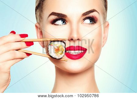 Beautiful girl with red lips and manicure eating sushi close-up. Smiled woman with perfect make up holding Sushi roll with chopsticks. Healthy Japanese food. Diet concept