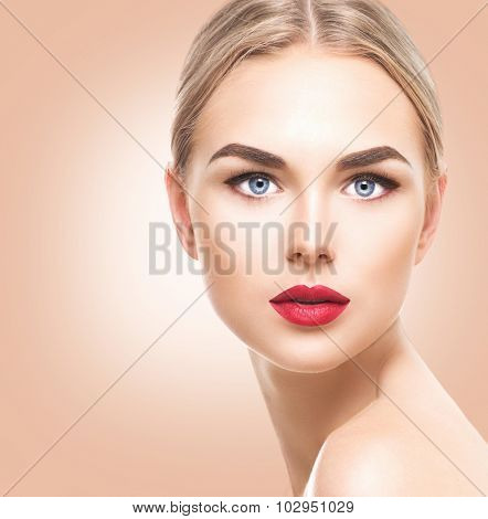 Attractive model girl face with perfect make-up looking at camera close up. Portrait of beauty young woman with blond hair and blue eyes. Beautiful female face with clear fresh skin. Pure Beauty model