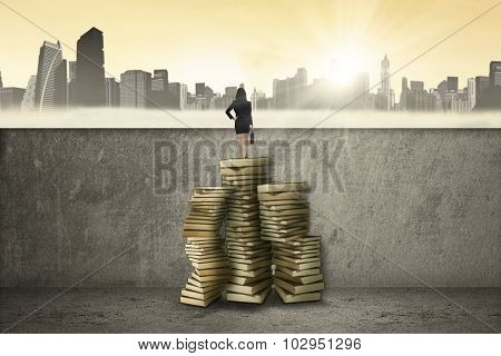 Woman Standing On Book And Looking At Town