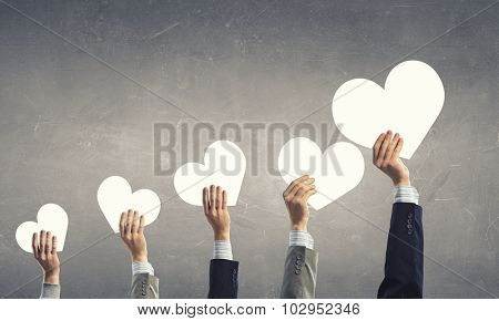 Group of people holding heart cards in raised hands