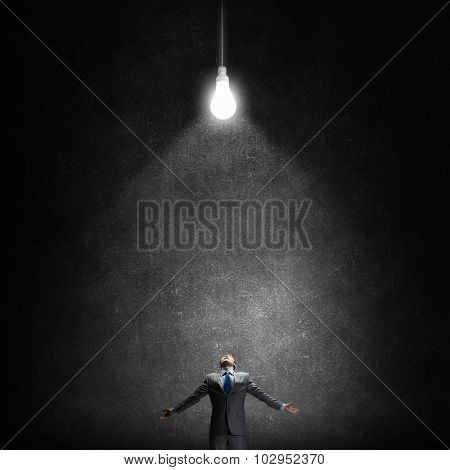 Businessman with hands spread apart and light bulb above