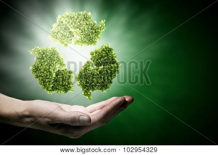Close up of hand holding green recycle sign