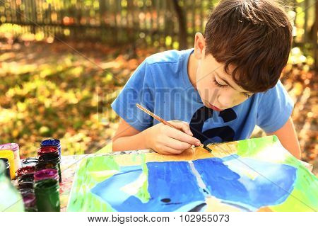Boy Paint A Picture  On The Autumn Background