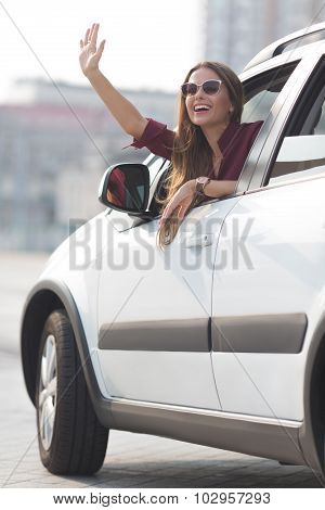 Beautiful lady waving from her car