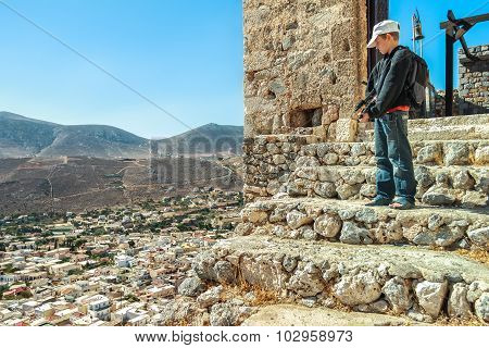 Teenage traveler standing high up on stone steps of ancient Byzantine Castle of Chora on Greek Kalym