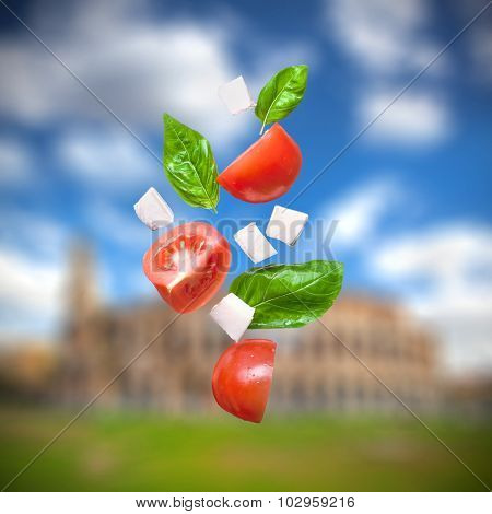 flying salad on colosseum on background - red tomatoes, pepper, cheese, basil, cucumber and olives