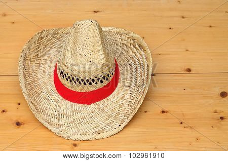Straw Hat With Red Ribbon On Wood Panel