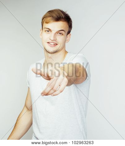 young handsome man on white background gesturing, pointing, posing emotional