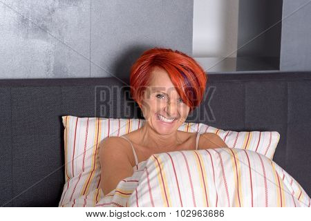 Happy Middle Aged Woman Lying In The Bed