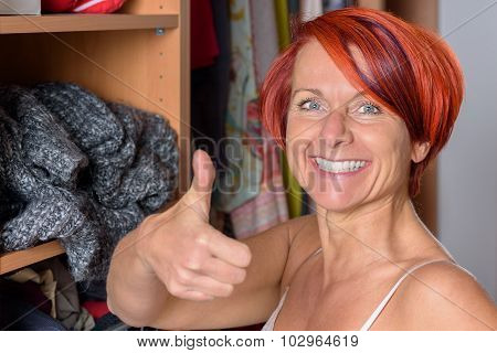 Happy Middle Aged Woman In Front Of Her Wardrobe
