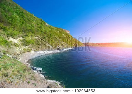 Coast of the big river under sunshine. Beautiful river bank with green trees and bushes